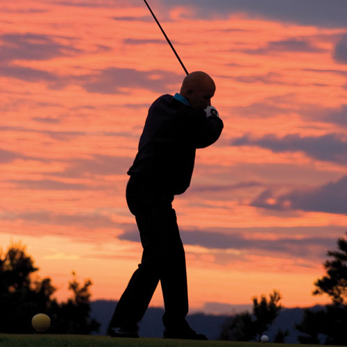 Mann spiller golf om kvelden på Kragerø Resort